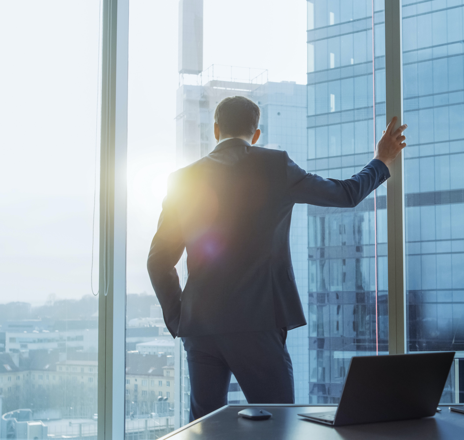 Shot of the Confident Businessman in a Suit in His Office Leaning Against Window Frame, Looking out of the Window Thoughtfully. Big City Business District Panoramic Window View.
